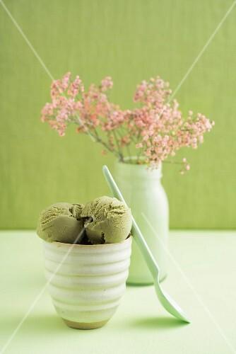 Grüntee-Eis im Becher vor Blumenvase mit Schleierkraut