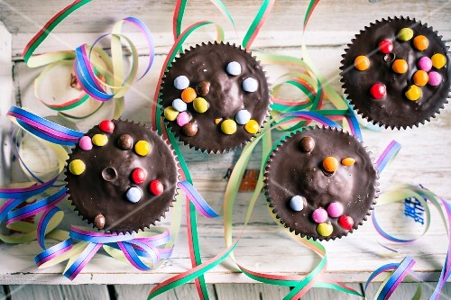 Muffins with chocolate glaze and colourful chocolate beans