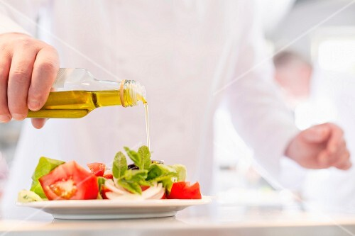 A chef pouring oil over a salad