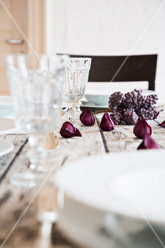 An autumnal laid table with wine glasses and purple flowers