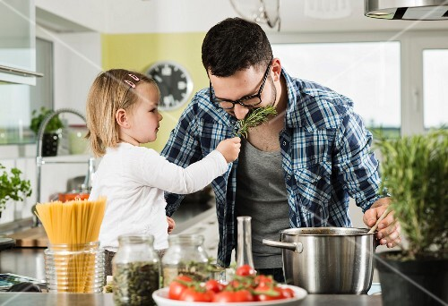 A father and daughter cooking in a kitchen
