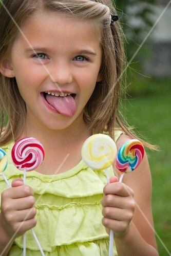 A little girl holding three lollipops