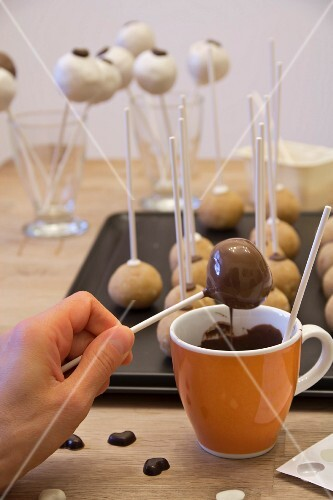 A woman dipping cake pops into chocolate glaze