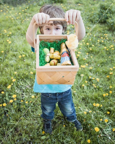 A little boy holding up his Easter basket of chocolate bunnies
