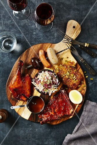 Grilled meats, sauces and a sausage skewer on a wooden chopping board
