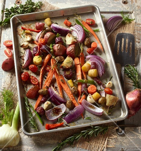 Roasted root vegetables with rosemary on a baking tray