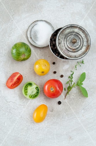 Colourful tomatoes, salt, black pepper, sage and thyme