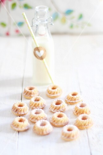 Mini Bundt cakes and a bottle of milk on a white wooden table