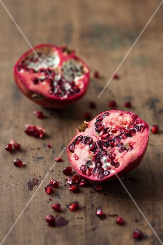 A halved pomegranate on a wooden surface
