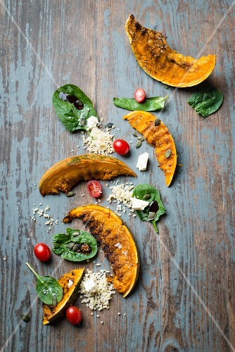 Grilled pumpkin wedges with a bulgur and spinach salad and feta cheese and wooden surface