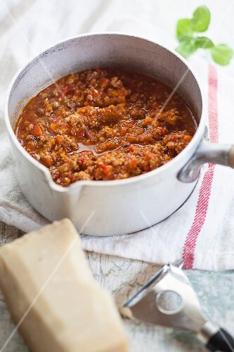 Bolognese sauce in pot with Parmesan cheese next to it
