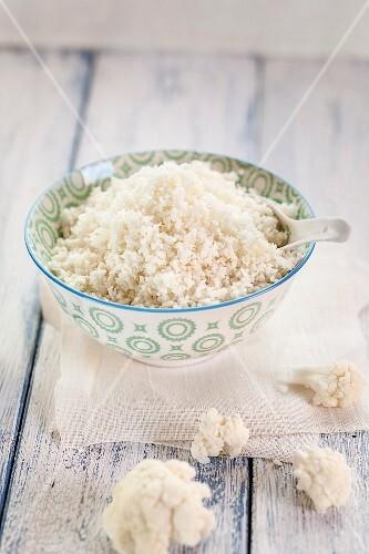 A bowl of cauliflower rice next to cauliflower florets