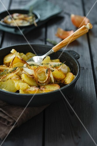 Fried potatoes with onion rings and thyme