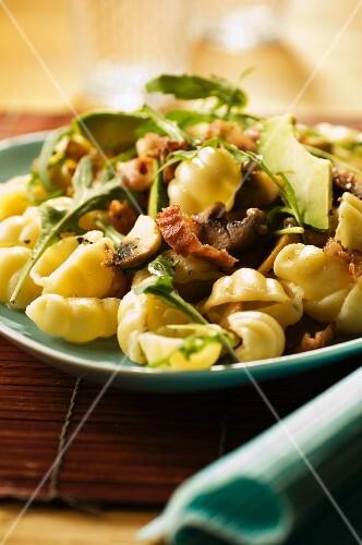 Gnocchi with bacon, avocado, garlic and fried mushrooms