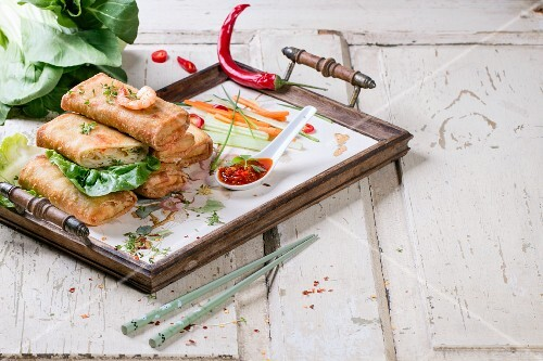 Spring rolls with vegetables and prawns served with a spicy sauce on a tray