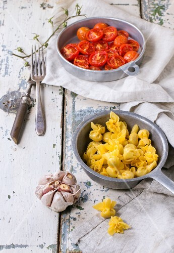 Sacchettini with baked tomatoes and garlic on an old wooden table