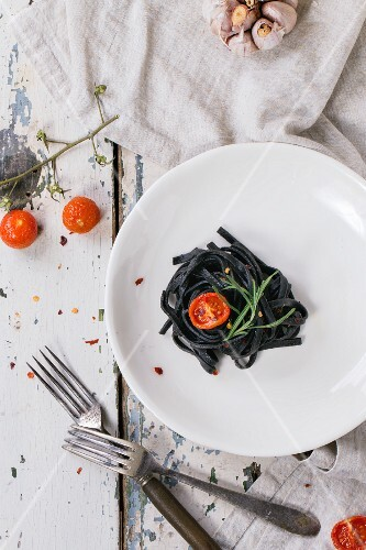 Black tagliolini with baked tomatoes and garlic on old wooden table