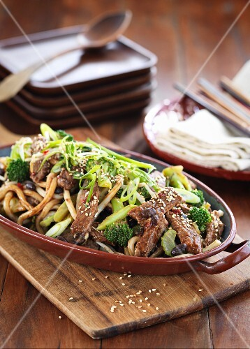 Beef with noodles, sesame seeds, broccoli and spring onions