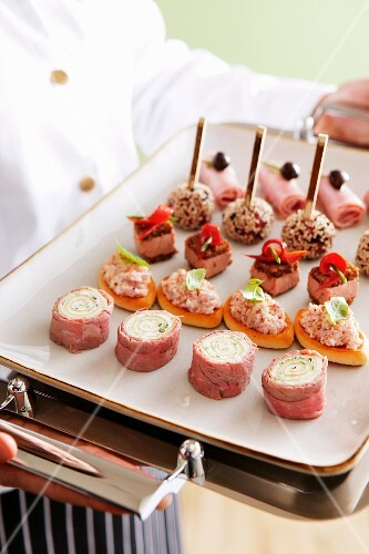 A chef holding a tray of savoury canapés