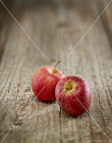 Two red apples on a wooden surface