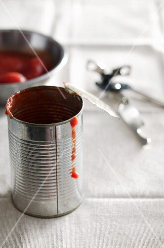 An empty tin of tomatoes with a tin opener