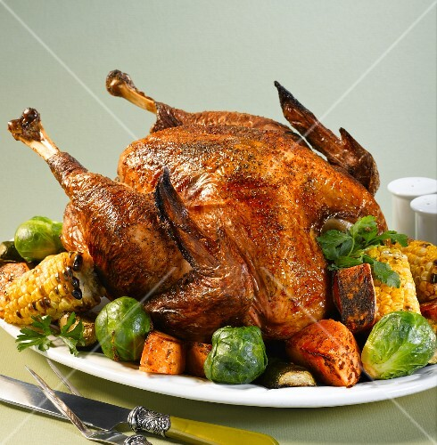 Roast turkey with Brussels sprouts, corn cobs and sweet potatoes