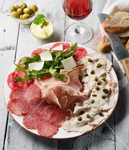 An Italian appetiser platter featuring Parma ham, Vitello tonnato, Carpaccio, salami, rocket and Parmesan cheese