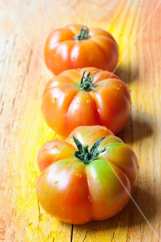 Three Sicilian tomatoes on a wooden surface