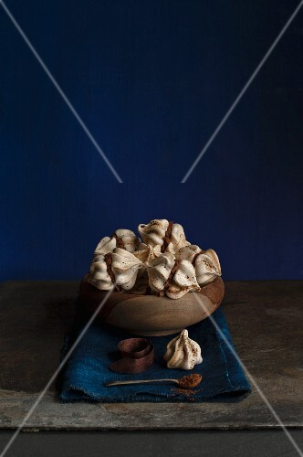 Mini meringues filled with coffee cream in a wooden bowl