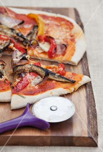 A vegetable pizza with peppers, aubergines and onions, sliced