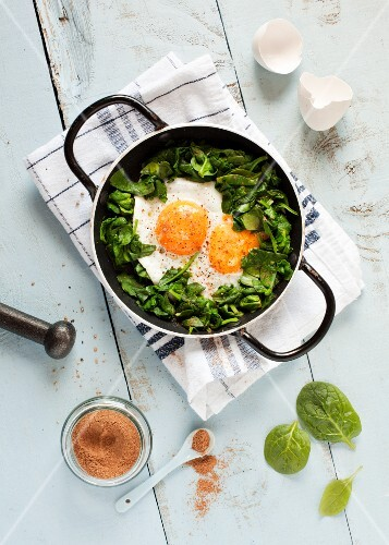 A double yolked egg with nutmeg on a spinach salad (seen from above)