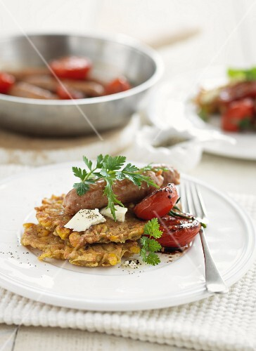 Sweetcorn and sweet potato fritters with sausages and tomatoes