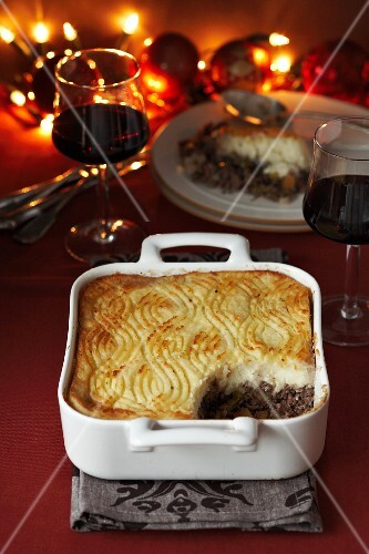 Shepherd's pie, with a portion missing, and two glasses of red wine (Christmas)