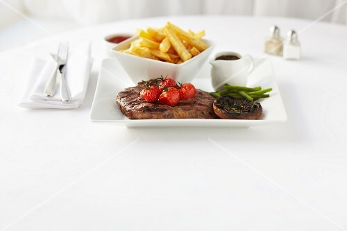 Steak with chips, pepper sauce, grilled tomatoes and mushrooms