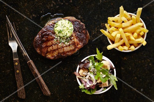 Grilled steak with garlic and herb butter served with chips and a salad