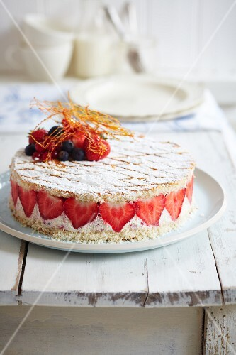 Strawberry fridge cake with mixed berries and caramel threads