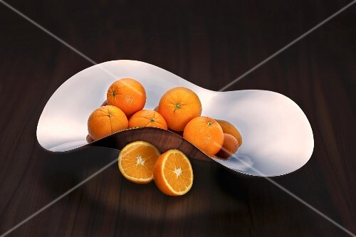 Oranges in a curved stainless steel dish