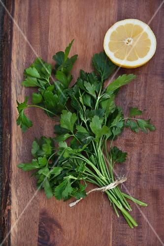 Flat leaf parsley with half a lemon on a wooden board