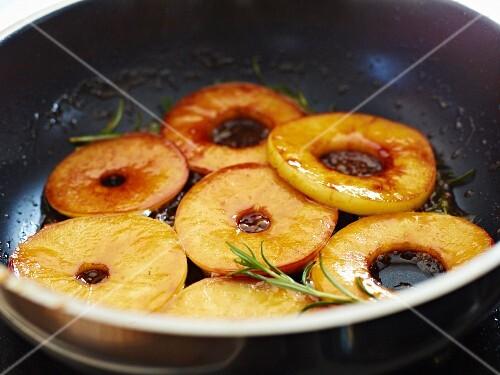 Apple rings being caramelised in a pan
