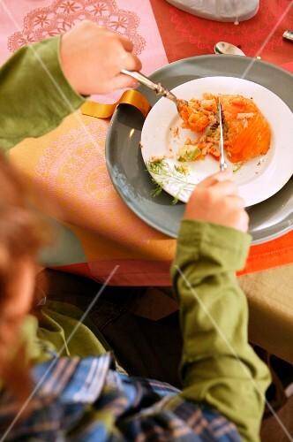 A boy eating a salmon dish for Christmas