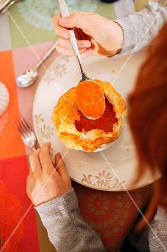 A child eating tomato soup with a puff pastry topping