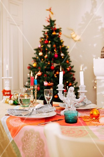 A table laid in front of a Christmas tree
