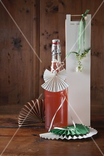 Bottle with hand-made paper angel tag and paper gift bag