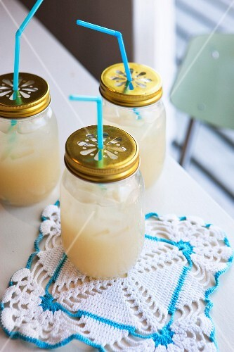 Jars with drinking straws pushed through lids and crocheted doily