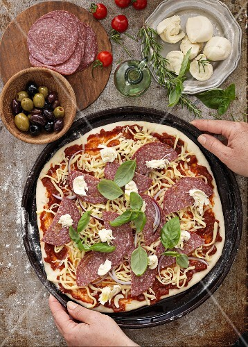 Hands holding an unbaked pizza with sausage and cheese surrounded by ingredients