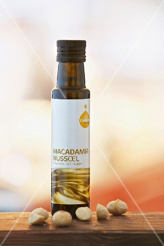 A bottle of macadamia nut oil and macdamia nuts on a wooden board