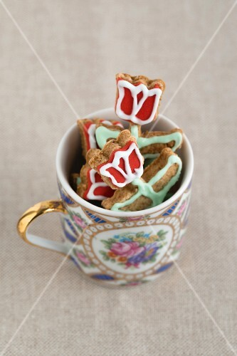 Iced, flower-shaped biscuits in a cup