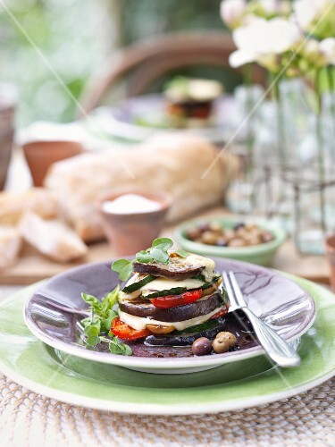 An aubergine tower with olives and mozzarella