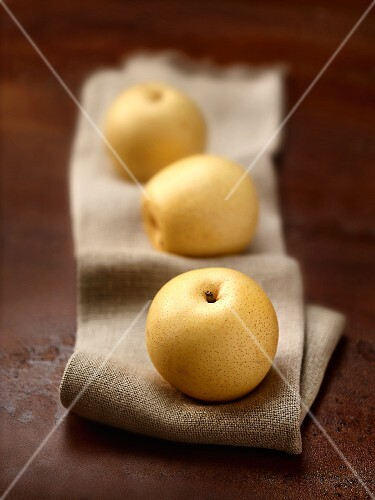 Three nashi pears on a linen cloth