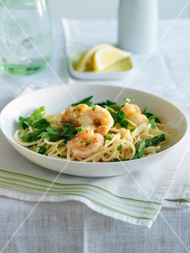 Spaghetti with prawns, asparagus and fresh parsley on a table with lemon slices and water
